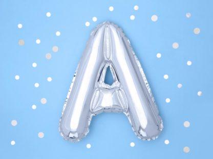 Srebrny balon foliowy w kształcie litery A na niebieskim tle