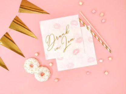 Serwetki i słomki papierowe na różowym tle