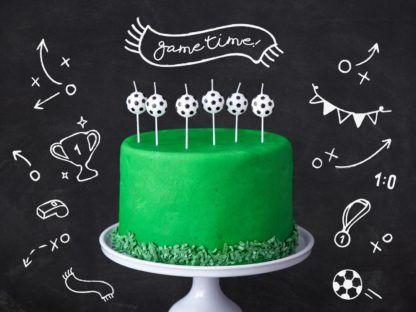 Świeczki w kształcie piłek do piłki nożnej na zielonym torcie