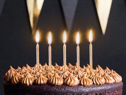 Złote świeczki na tort, zapalone
