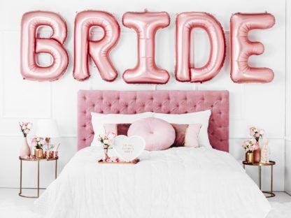 """Napis """"BIRDE"""" z balonów foliowych liter w kolorze złotego różu"""