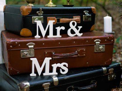 """Drewniany napis """"Mr&Mrs"""" na walizkach podróżnych"""