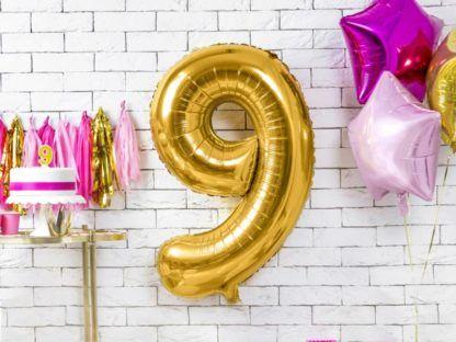 Złoty balon foliowy w kształcie cyfry 9 na ścianie