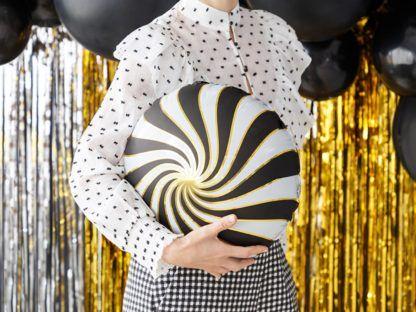 Kobieta z okrągłym czarno-złotym balonem