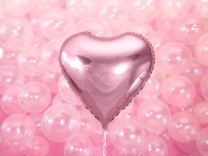 Różowy balon w kształcie serca na tle przezroczystych balonów