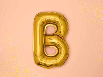 Złoty balon foliowy w kształcie litery B na różowym tle
