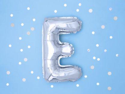 Srebrny balon foliowy w kształcie litery E na niebieskim tle