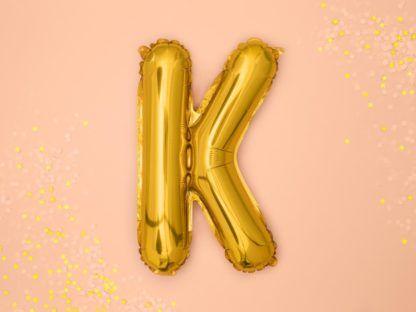 Złoty balon foliowy w kształcie litery K na różowym tle