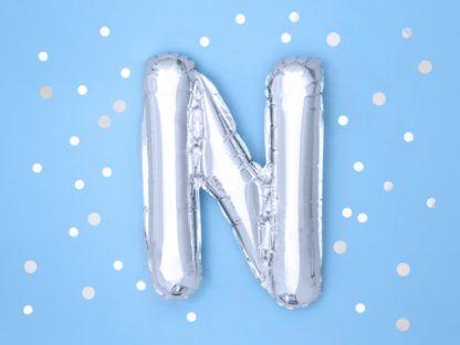 Srebrny balon foliowy w kształcie litery N na niebieskim tle