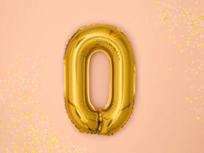 Złoty balon foliowy w kształcie litery O na różowym tle
