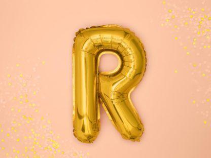 Złoty balon foliowy w kształcie litery R na różowym tle