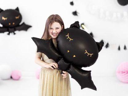 Dziewczynka z balonem foliowym w kształcie nietoperza