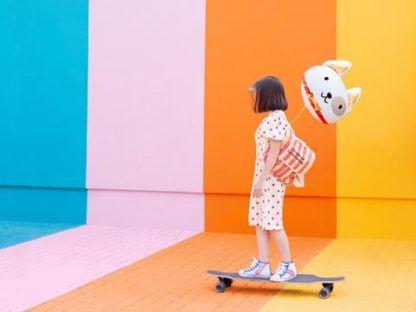 Dziewczyna na deskorolce z balonem foliowym w kształcie psa