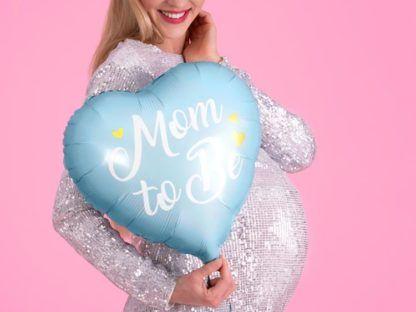 Kobieta w ciąży z niebieskim balonem foliowym