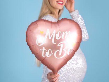 Kobieta w ciąży z różowym balonem foliowym w kształcie serca