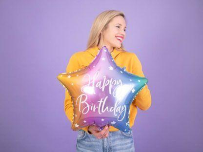 """Kobieta z tęczowym balonem foliowym w kształcie gwiazdki z napisem """"happy birthday"""""""