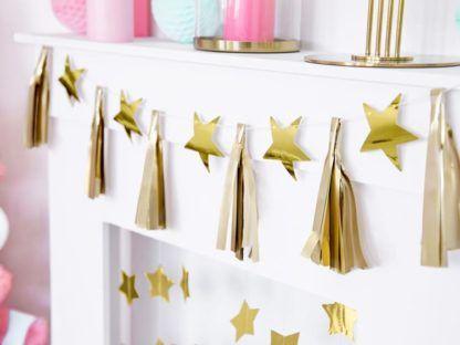 Rozwieszona złota girlanda z gwiazdkami i frędzlami