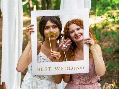 Kobiety trzymające ramkę do zdjęć na wesele