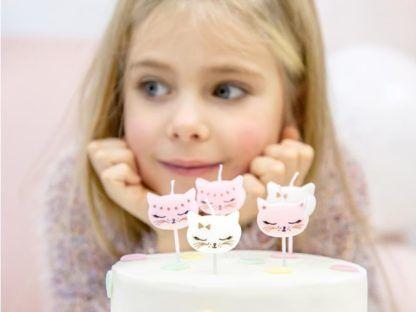 Dziewczynka z tortem i świeczkami w kształcie kotków