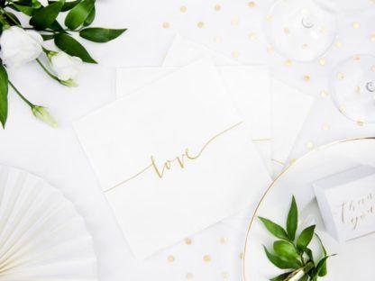 Białe serwetki ze złotym napisem