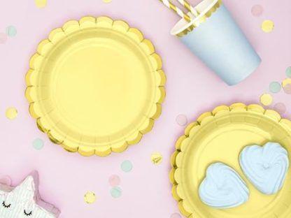 Żółte talerzyki papierowe i niebieski kubeczek