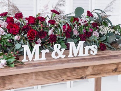 """Drewniany napis """"Mr&Mrs"""" na stole na tle kwiatów"""