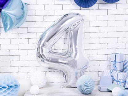 Srebrny balon foliowy w kształcie cyfry 4 na ziemi