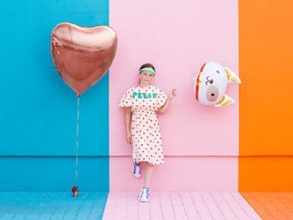 Dziewczyna z balonami foliowymi w kształcie serca i psa