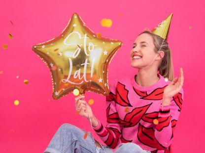 Kobieta ze złotym balonem foliowym na urodzinach