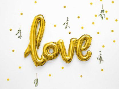 """Złoty balon w kształcie napisu """"love"""" na tle konfetti"""