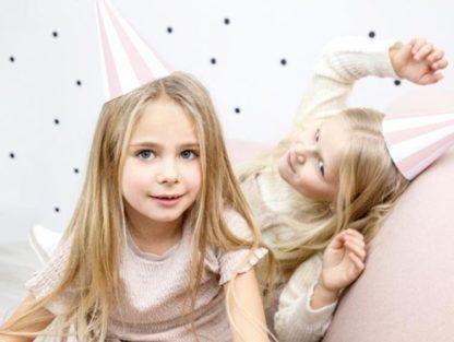 Dziewczynki w biało-różowych czapeczkach papierowych