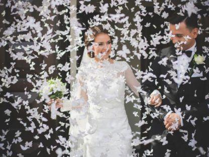 Para młoda w otoczeniu konfetti w kształcie motylków
