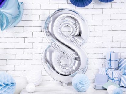 Srebrny balon foliowy w kształcie cyfry 8 na ziemi