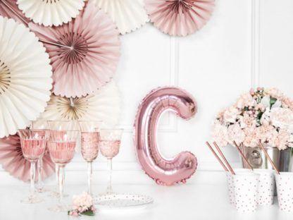 Różowe złoto balon foliowy w kształcie litery C na stole