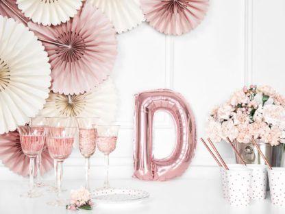 Różowe złoto balon foliowy w kształcie litery D na stole