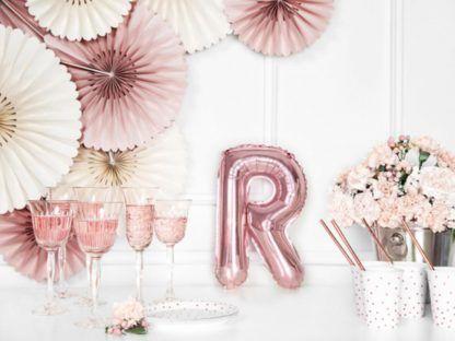 Różowe złoto balon foliowy w kształcie litery R na stole
