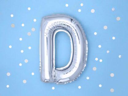 Srebrny balon foliowy w kształcie litery D na niebieskim tle