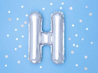 Srebrny balon foliowy w kształcie litery H na niebieskim tle