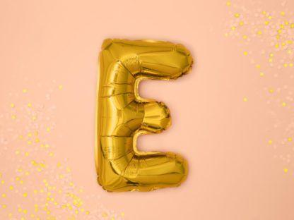 Złoty balon foliowy w kształcie litery E na różowym tle