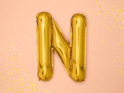 Złoty balon foliowy w kształcie litery N na różowym tle