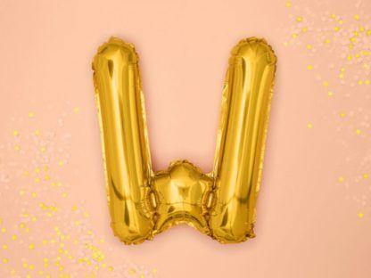 Złoty balon foliowy w kształcie litery W na różowym tle